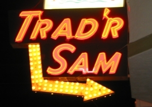 Neon sign in front of Trad'r Sam