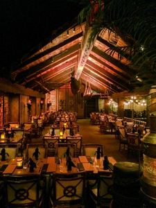 A dining room under an A-frame structure, with outrigger canoes overhead, at Tonga Room in San Francisco