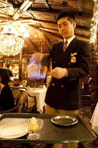 Staff member making Baked Alaska for dessert at Trader Vic's in Tokyo