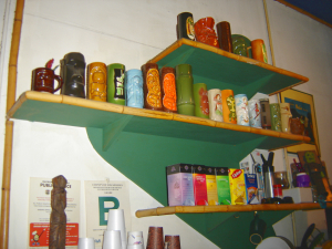 Tiki mugs on a shelf at Cacao Coffee House