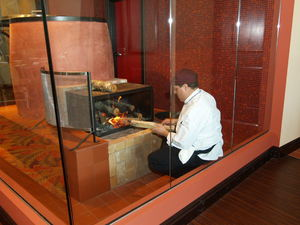 Chef Juan placing firewood into Chinese oven at Trader Vic's in Destin