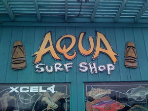 Bosko tikis flank the sign for Aqua Surf Shop in San Francisco