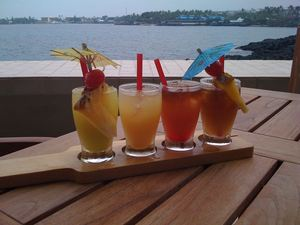 """Tiki Taster"" of Mai Tais at the outdoor bar at Don the Beachcomber in Kailua-Kona. L-to-r: Green Flash (with Midori), Topless (float of coconut rum), Volcanic (with grenadine), and Original."