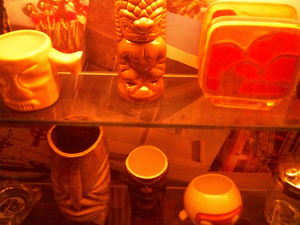 Tiki mugs and collectibles on display under the bar at Hula's Modern Tiki in Phoenix