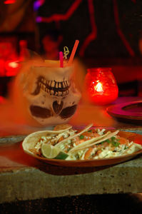 Food and cocktail in a skull mug at Grass Skirt Tiki Room in Columbus