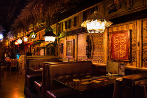 The narrow back hallway with intimate booth seating at The Shameful Tiki Room in Vancouver
