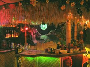The bar, with glowing moon mural and lava rock shelves, at Kanaloa Lounge in Calgary